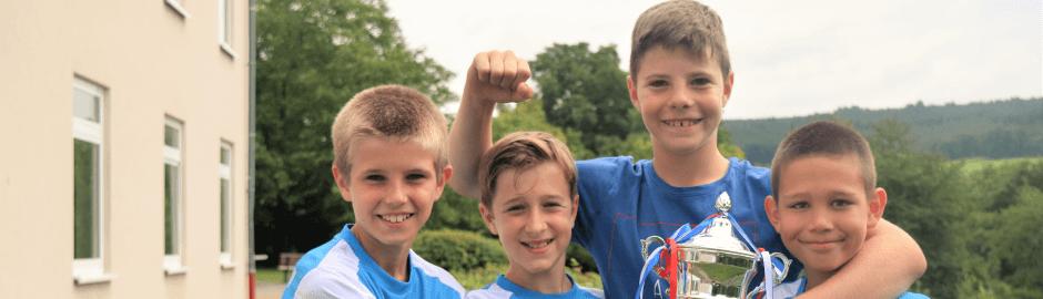 Fußballtrainingslager mit Jungs in Siegerpose
