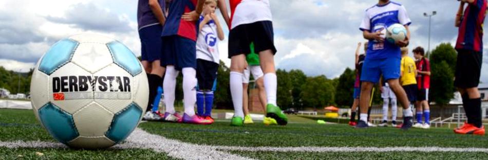 Kinder mit Ball beim Fußball in den Ferien